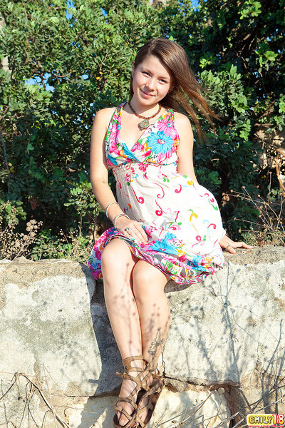Emily 18 sits on a rock outdoors on touching the brush cute flowered dress and she smiles at one's disposal th