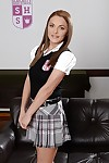 European schoolgirl Dominica Asmodeus modelling fully clothed on leather couch