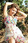 Emily 18 sits on a rock outdoors on touching the brush cute flowered dress and she smiles at one\